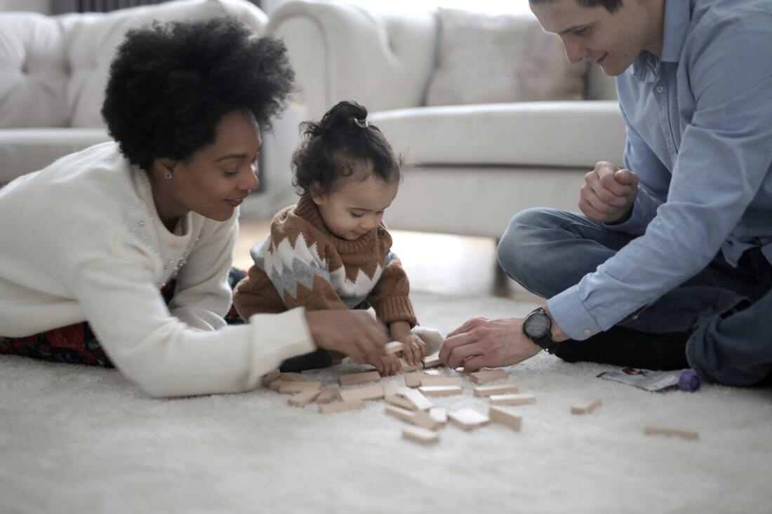 Photo of Family Playing with Child